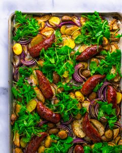 Spicy sausage and apple bake on a sheet pan with potatoes, onions, and arugula.