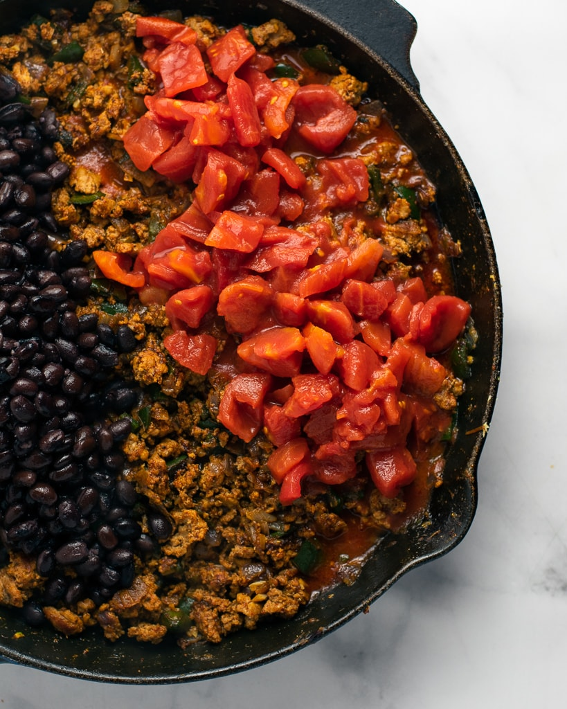 Black beans and tomatoes in a skillet with turkey enchilada filling.