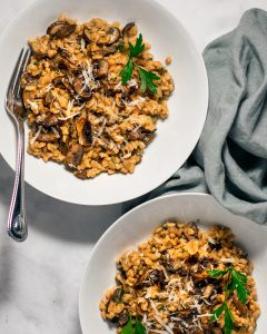 Two white bowls of farro risotto with mushrooms.