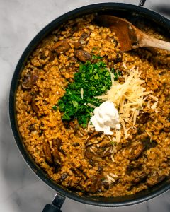 A skillet of farro risotto with sour cream, parmesan and parsley.