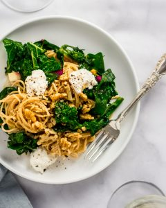 Overhead shot of Whole-Wheat Pasta with Walnuts, Greens & Ricotta on a white plate with a silver fork.