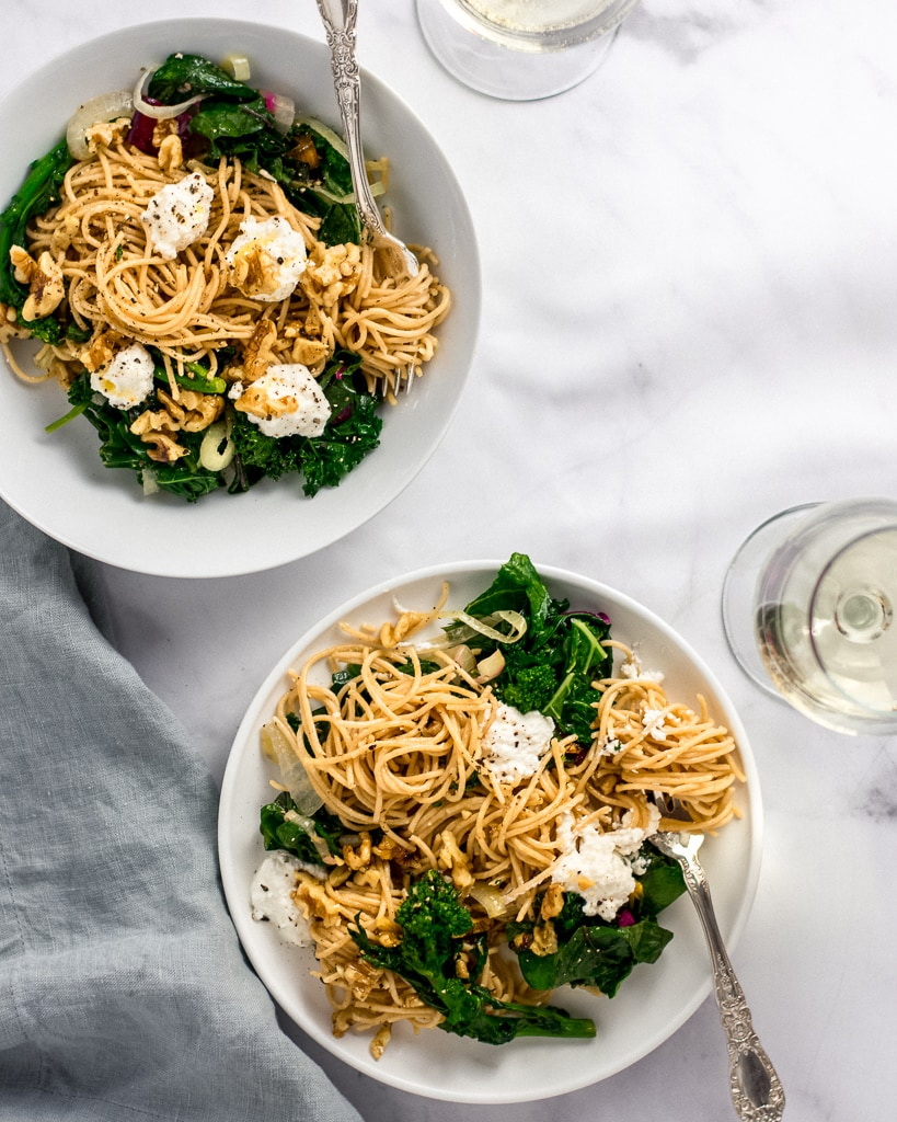 Overhead shot of two white bowls of Whole-Wheat Pasta with Walnuts, Greens & Ricotta with silver forks and two glasses of white wine.