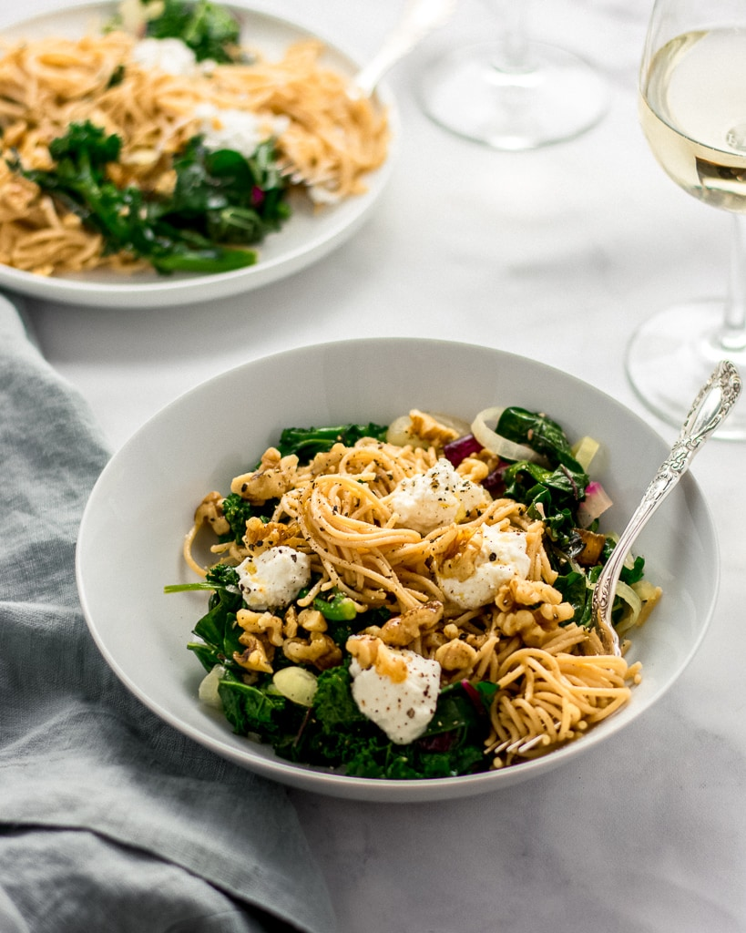 Three-quarters shot of two white bowls with Whole-Wheat Pasta with Walnuts, Greens & Ricotta and a silver fork.
