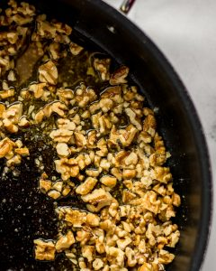 Close-up shot of walnuts in oil in a black skillet.