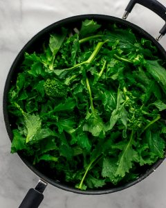 Overhead shot of raw broccoli rabe in a black skillet.
