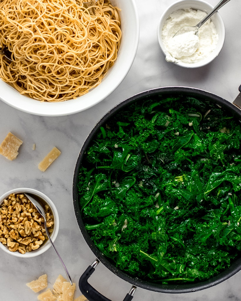 Overhead shot of whole-wheat pasta, ricotta, sautéed greens, walnuts, and parmesan in separate bowls.