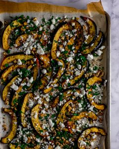 Overhead shot of roasted winter squash on a sheet pan with walnuts & feta.