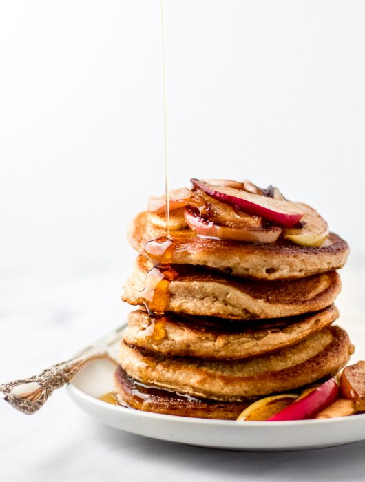 Pouring maple syrup onto a stack of whole wheat pancakes.