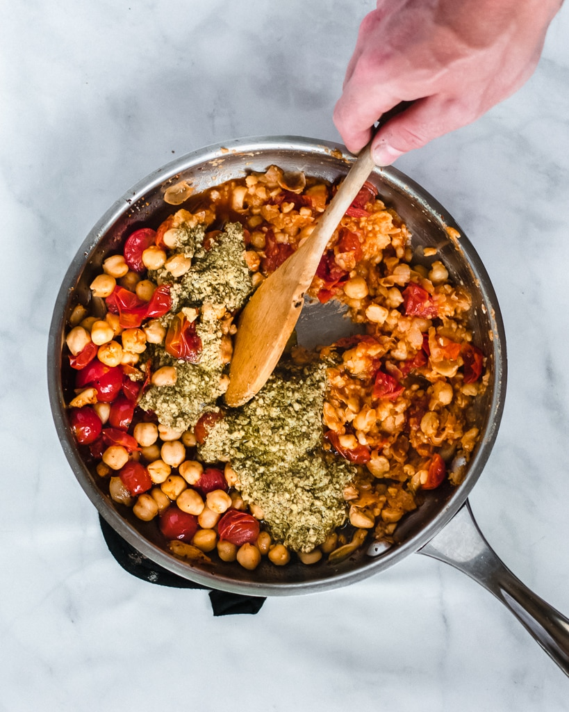 Tomatoes, garlic, chickpeas, and pesto in skillet