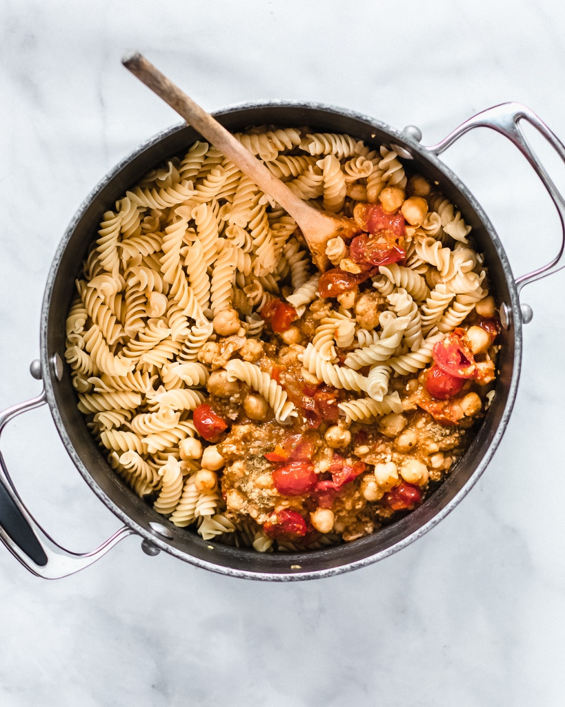 Chickpea pesto pasta in large pot with wooden spoon