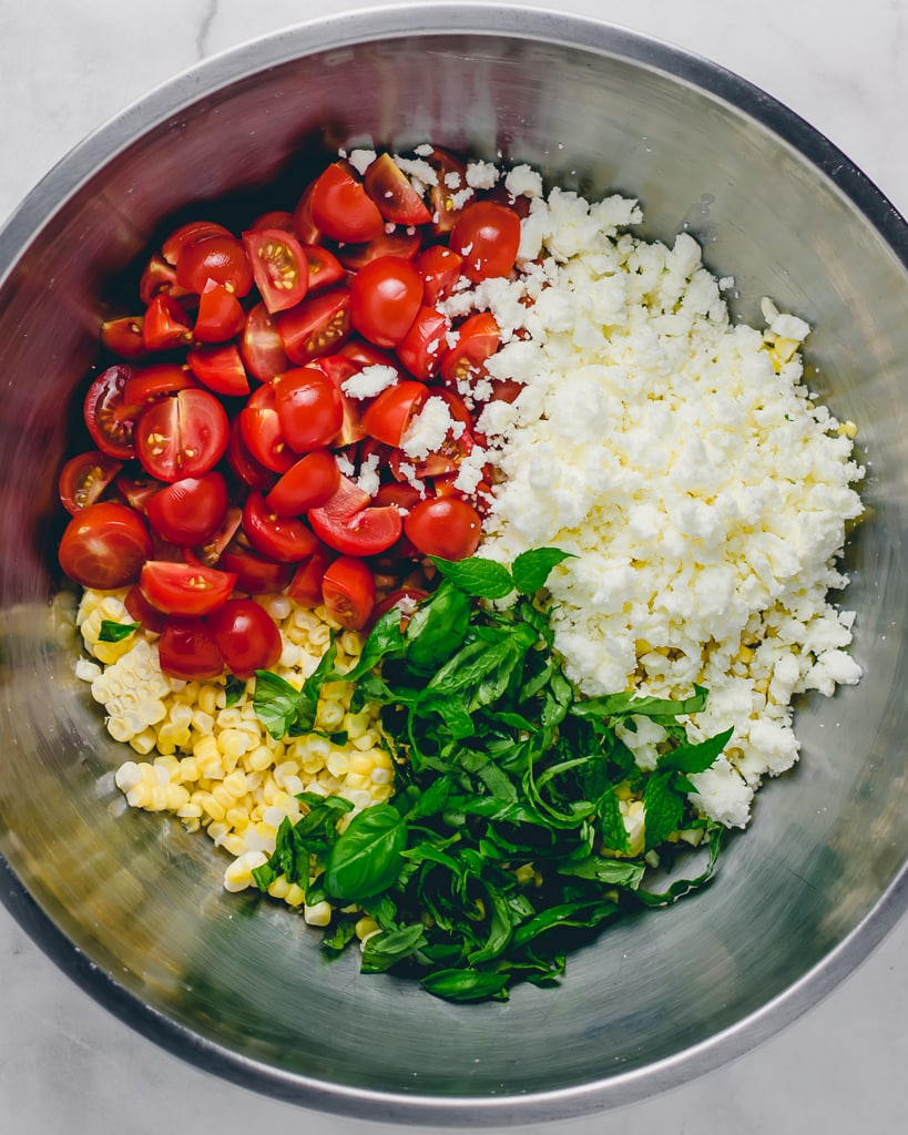 Tomatoes, feta, herbs and corn in a silver bowl