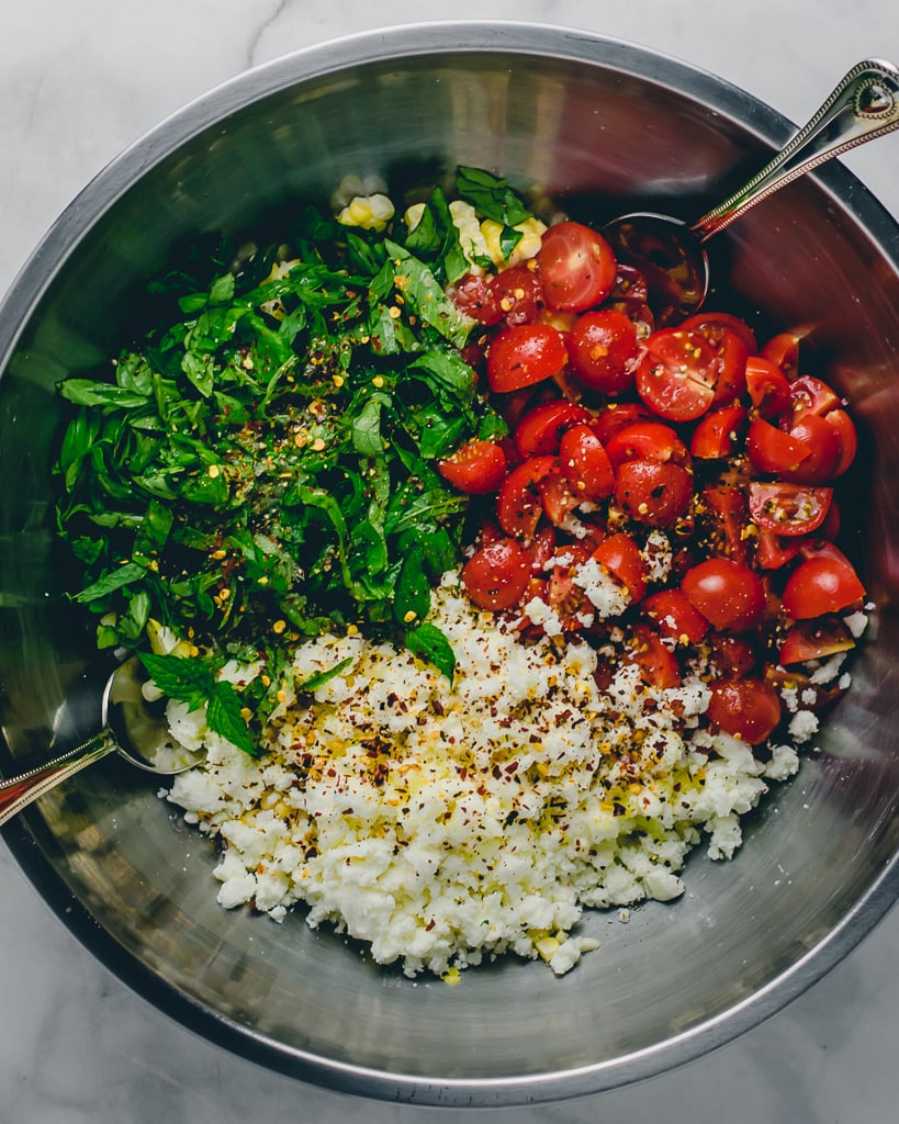Tossed corn salad with tomatoes, feta, and herbs with lime juice in a silver bowl