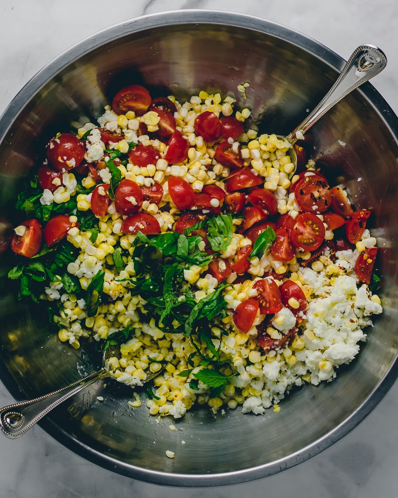 Tossed corn salad with tomatoes, feta, and herbs in a silver bowl