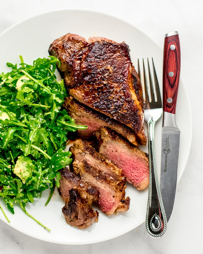 Steak with Arugula Salad on plate with knife and fork
