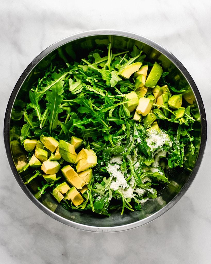 Arugula salad with avocado, Parmesan cheese, and lemon in bowl