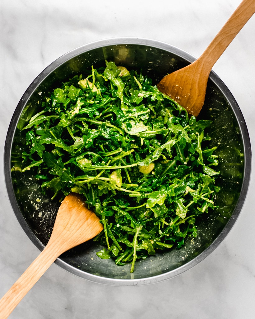 Tossed arugula salad with avocado, Parmesan cheese, and lemon in bowl