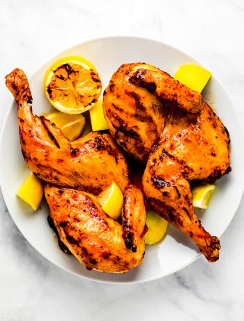 Whole grilled hot-honey lemon butter chicken on plate with lemons