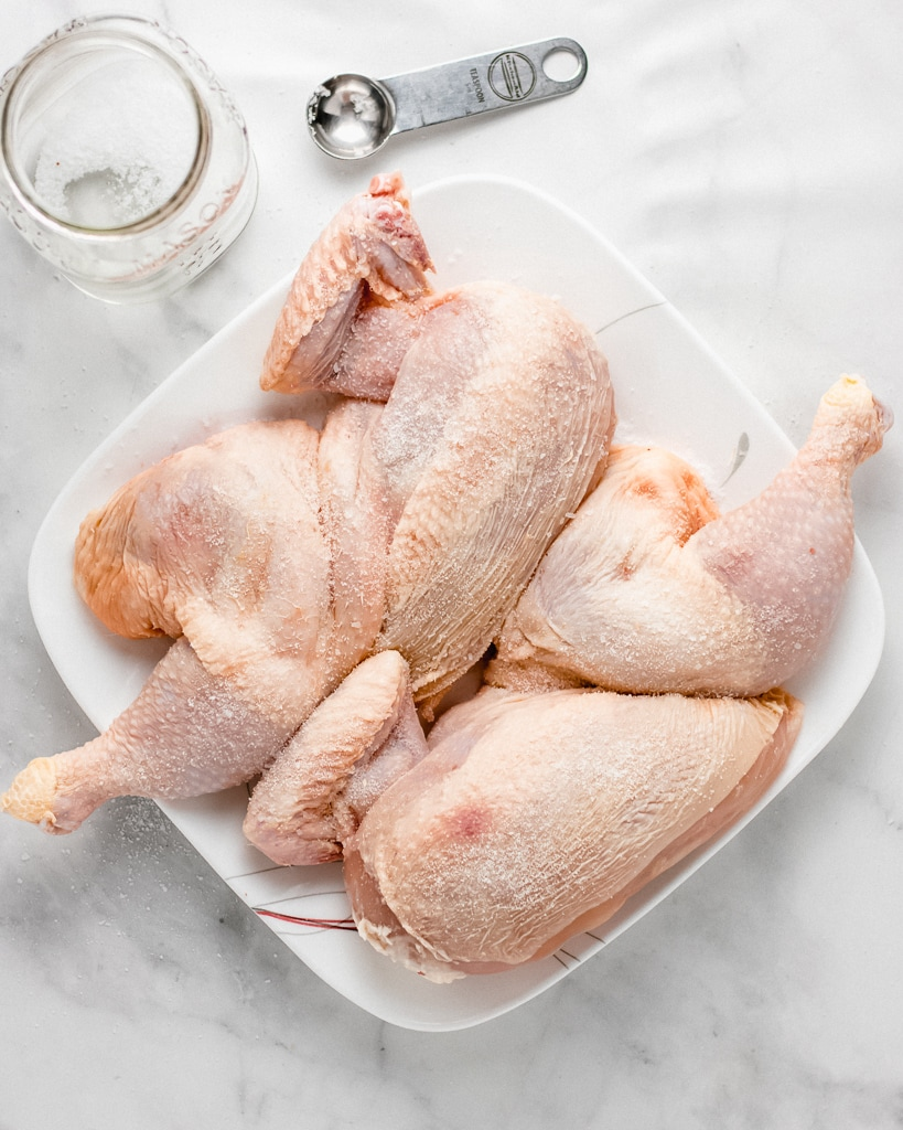 Raw whole chicken on plate with salt