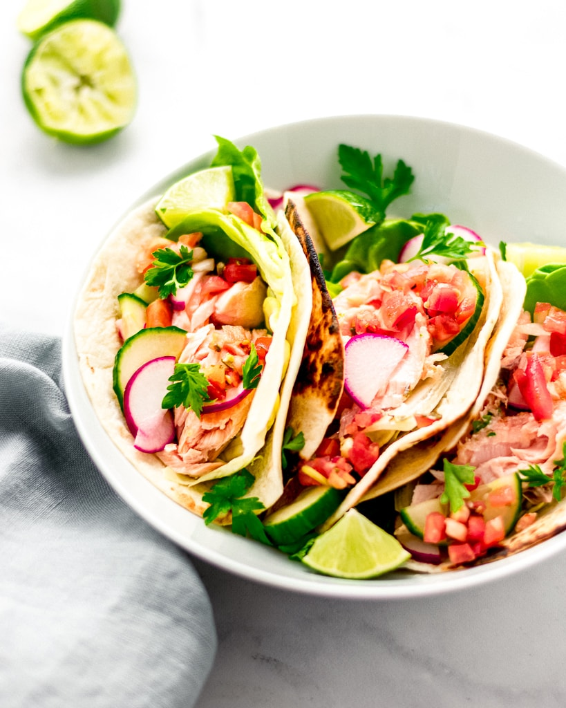 3 salmon tacos in a white bowl topped with radish and cucumber slaw