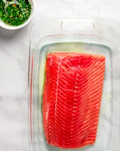 Raw salmon fillet in a glass baking dish with cilantro and olive oil sauce on the side