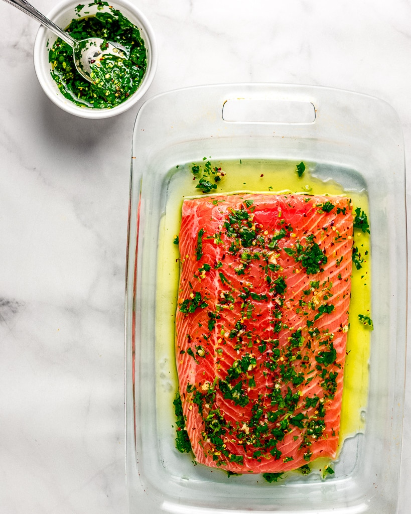 Raw salmon fillet in a glass baking dish with cilantro and olive oil