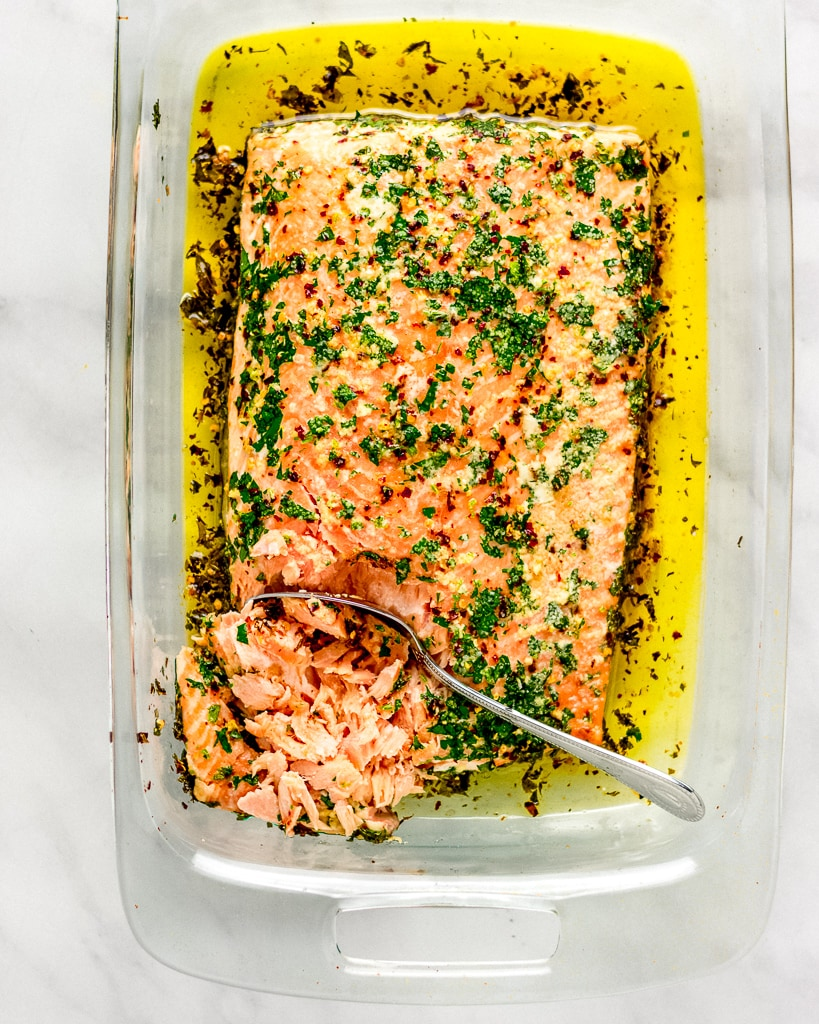 Baked whole salmon fillet with cilantro and olive oil in a glass dish.