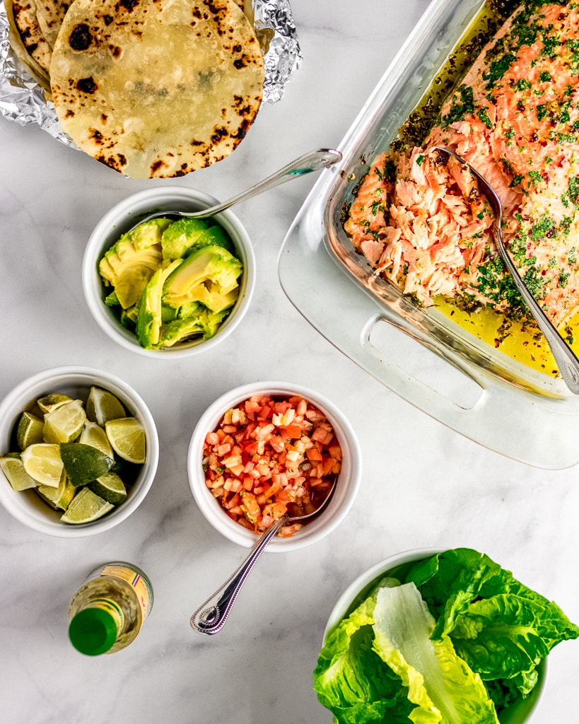Overhead shot of tortillas, cooked salmon in a glass dish, and sliced avocado, limes, pico de gallo, and romaine lettuce in bowls
