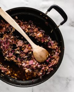 onions and garlic in skillet with white wine and wooden spoon
