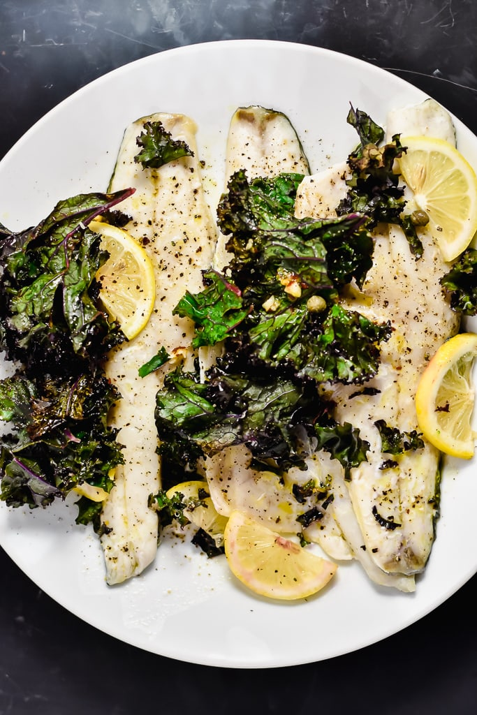 White fish on a white plate with kale and lemon
