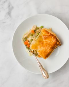 a slice of chicken pot pie on a plate with a silver spoon