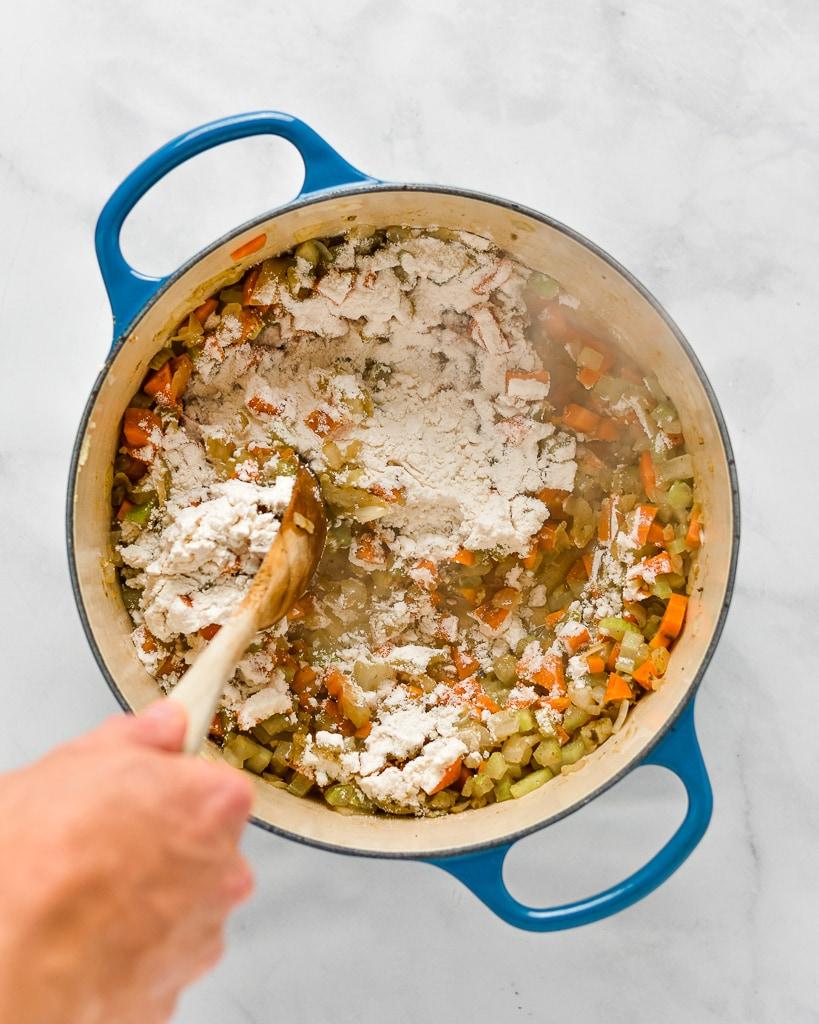 adding white wine to a pot of chicken pot pie