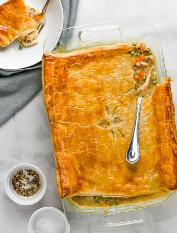 chicken pot pie in a casserole dish with a silver spoon