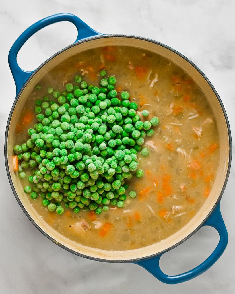 adding frozen peas to a pot of chicken pot pie