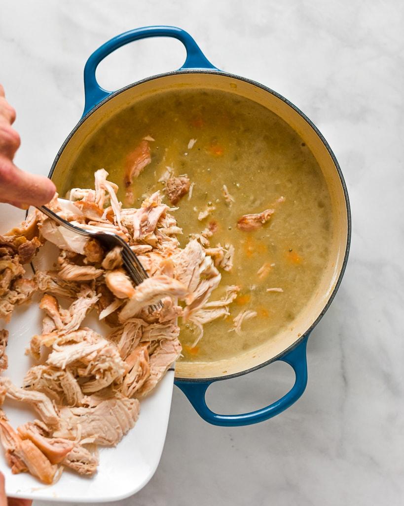 adding rotisserie chicken to a pot of chicken pot pie