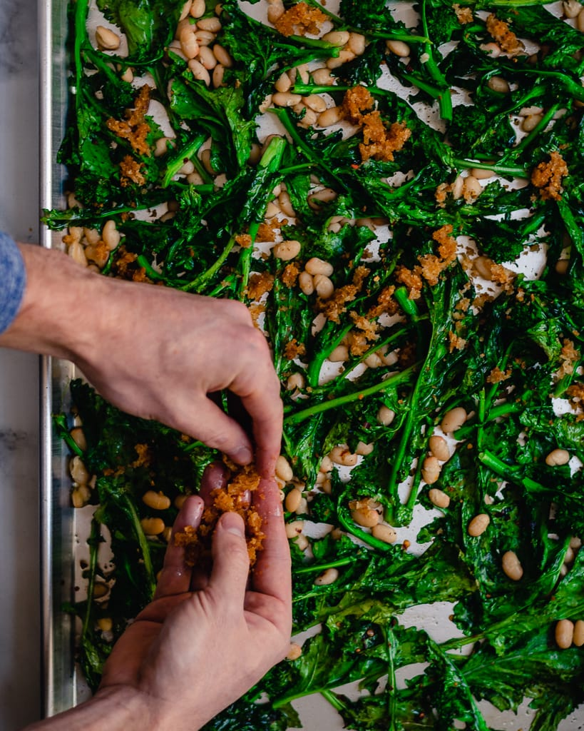adding cheddar breadcrumbs to broccoli rabe and beans on sheet pan