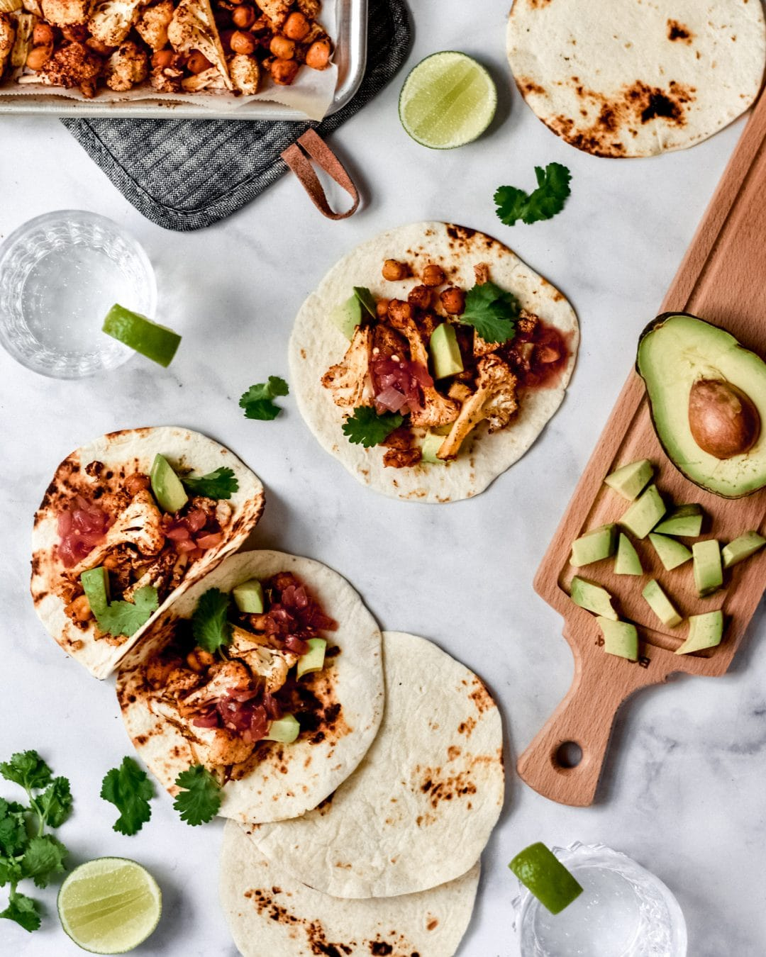 3 roasted cauliflower and chickpea tacos with avocado and a glass of seltzer