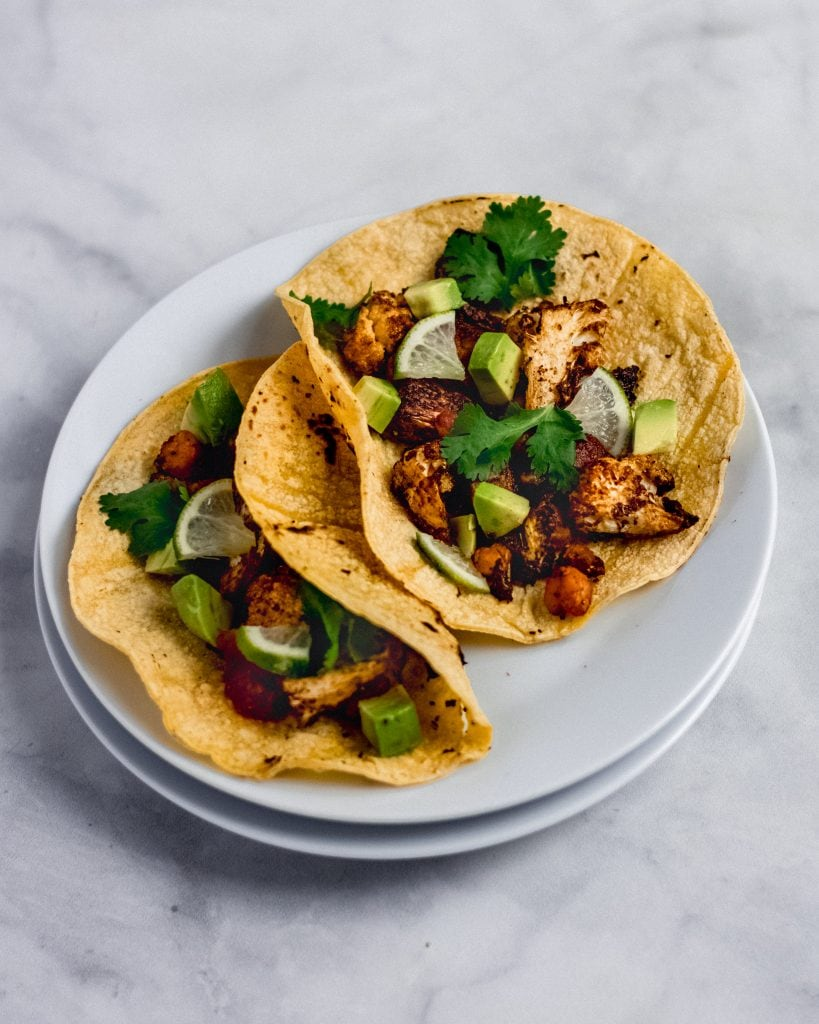 2 roasted cauliflower and chickpea tacos on a plate