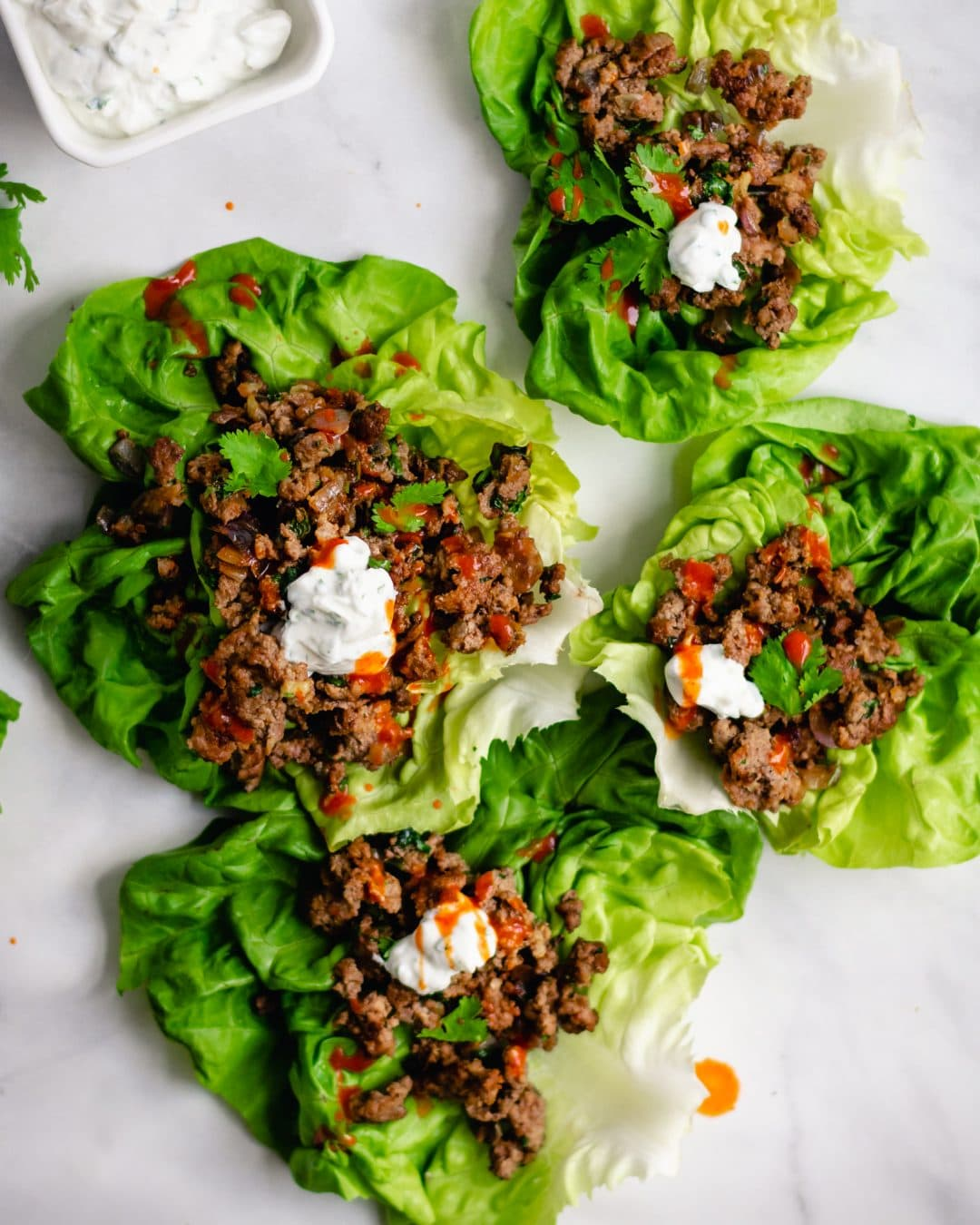 overhead shot of 4 thai beef lettuce wraps with herby yogurt