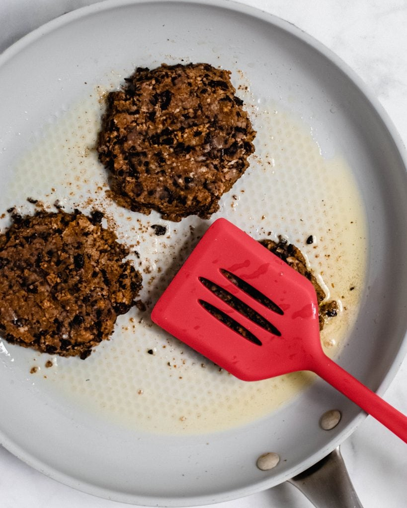 black bean burgers in a skillet with a red spatula