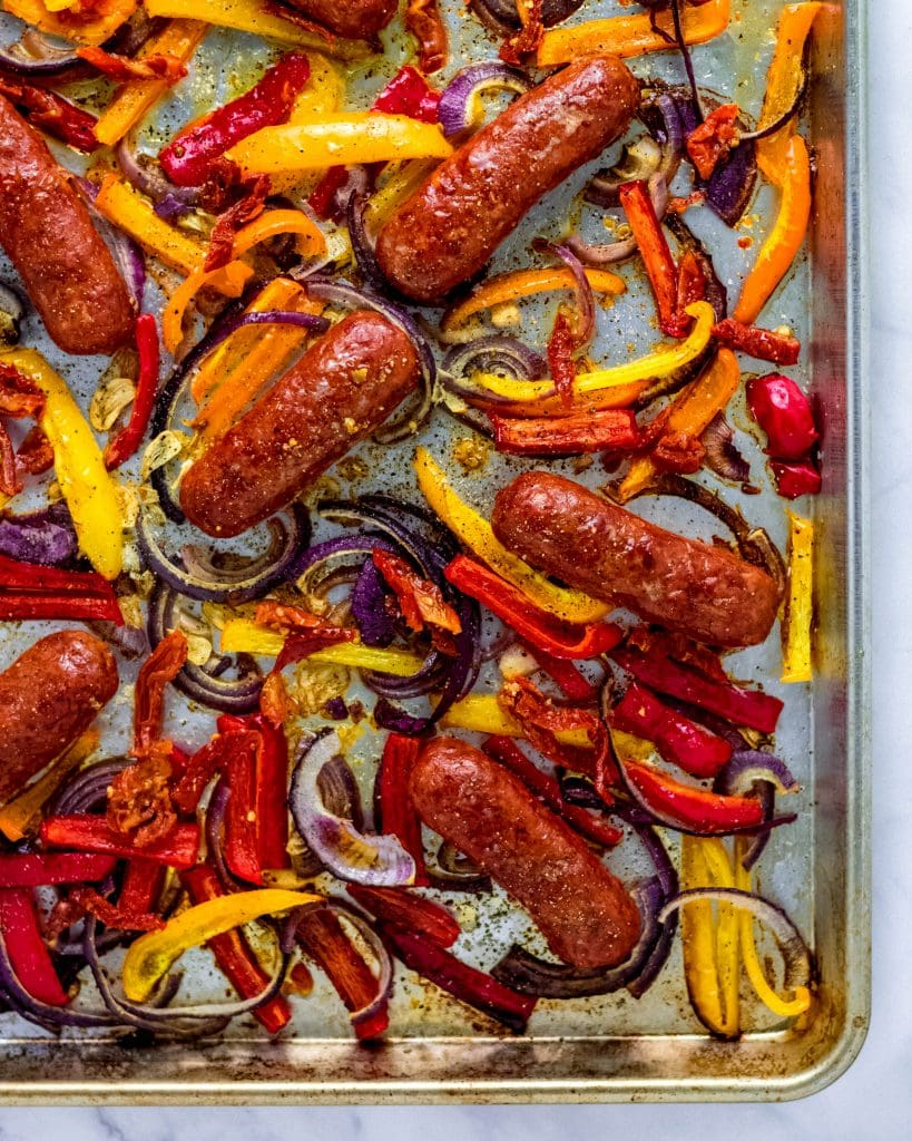 close up of cooked sausage and peppers on a sheet pan