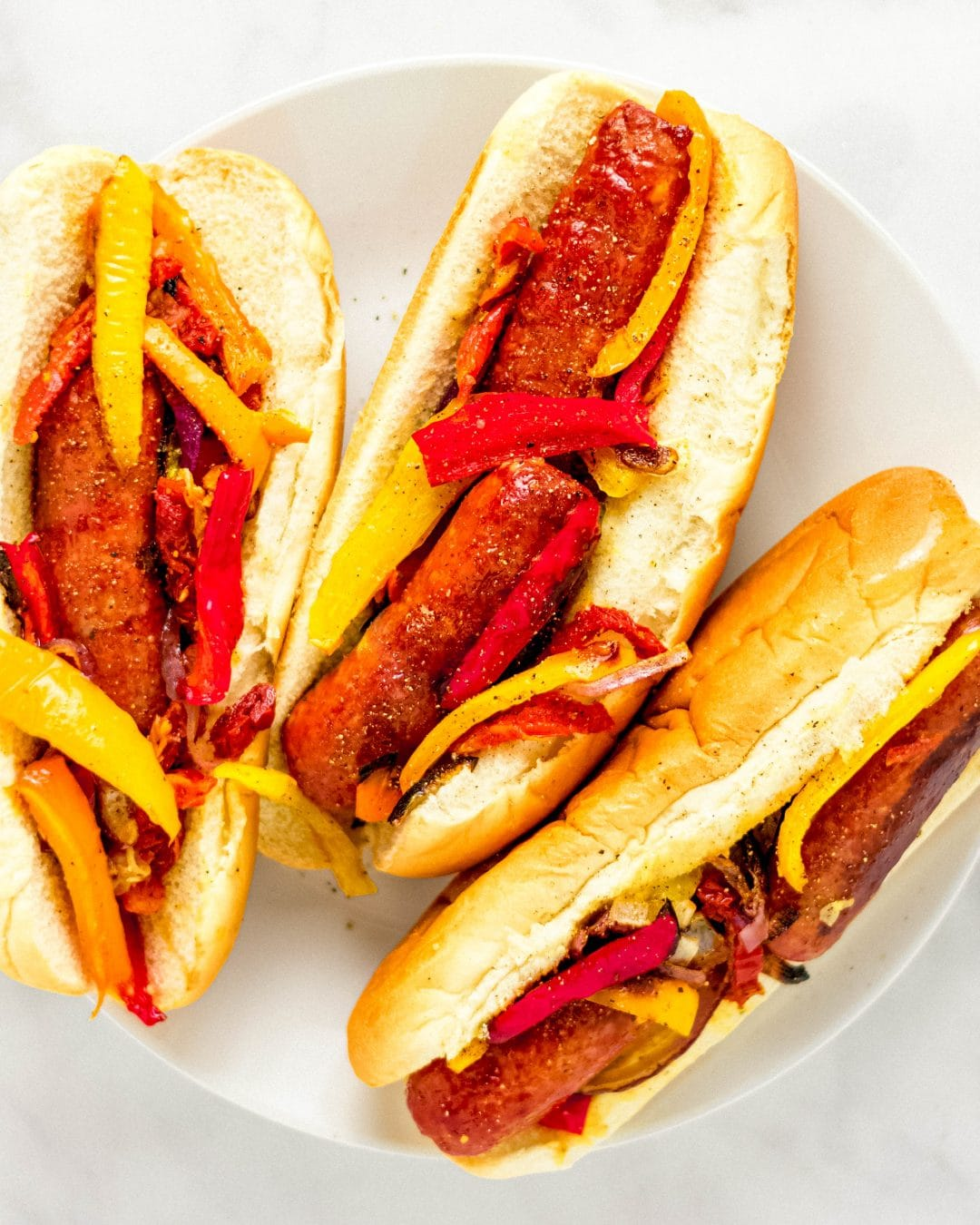 three buns with sausage and peppers on a plate