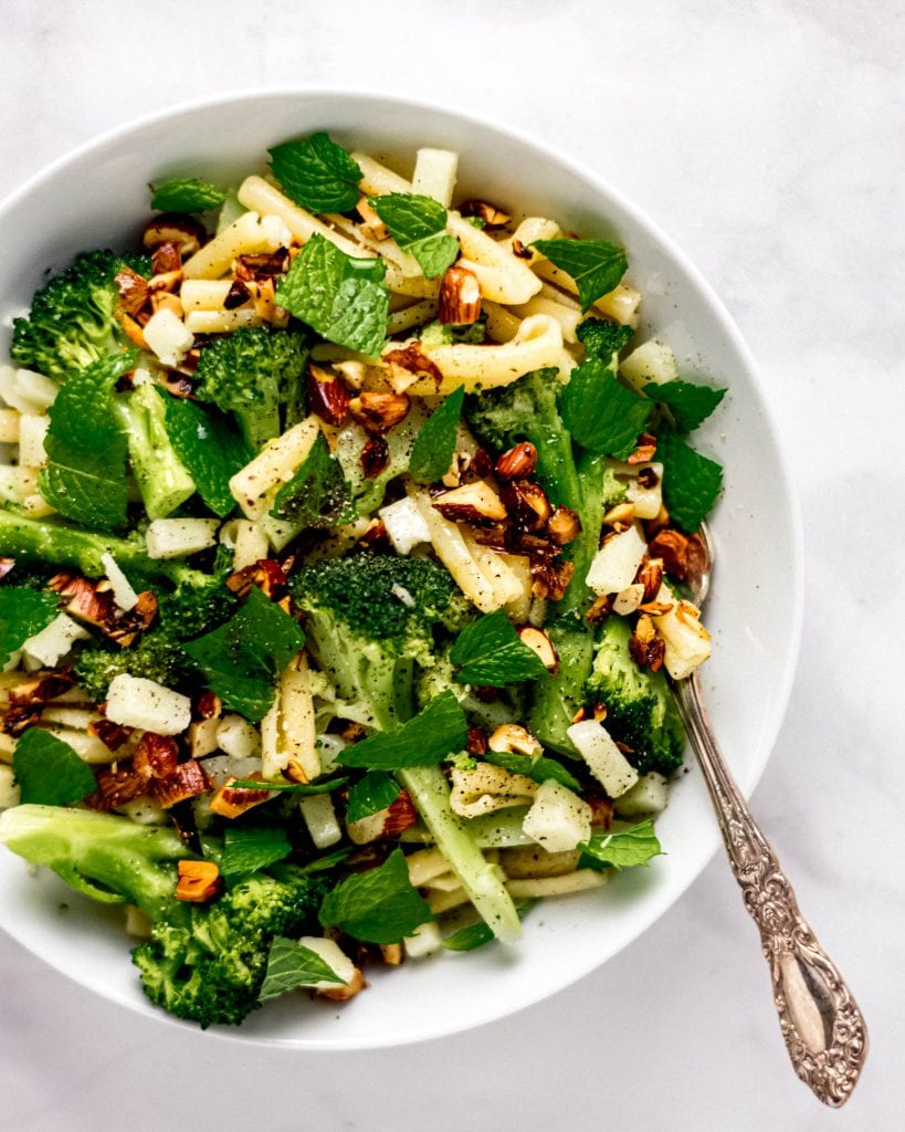 close up of broccoli pasta salad in a white bowl