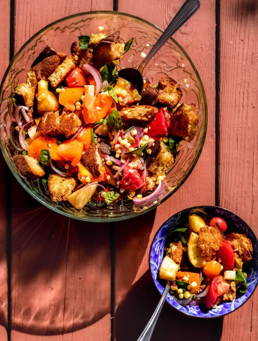 panzanella in a glass bowl and a smaller serving in a blue bowl